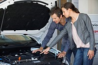 Couple looking at car engine in showroom (thumbnail)