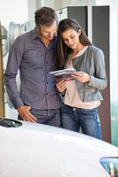 Happy couple looking at car catalog in showroom (thumbnail)