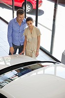 Couple looking at a car at a showroom