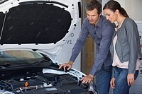Couple looking at car engine in showroom