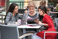 Young man with two young women looking at menu in a restaurant (thumbnail)