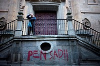 A man touches his head by a graffiti that reads 'Pensad!' that means 'think' in Spanish, in Salamanca, Spain. The Old City of Salamanca was declared a...
