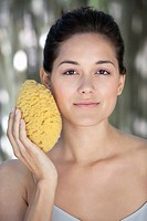 Beautiful young woman holding a bath sponge on her face (thumbnail)