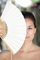 Beautiful young woman holding a Chinese fan in front of her face (thumbnail)