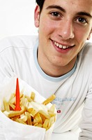 Portrait of a young man holding a packet full of French fries smiling
