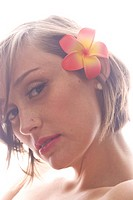 Portrait of young woman with a flower pin in her hair and a nose piercing