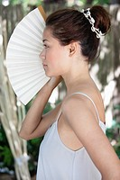 Side profile of a beautiful young woman holding Chinese fan on her face