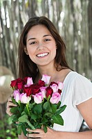 Portrait of a young woman holding bunch of colorful roses