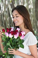 Happy young woman looking at bunch of colorful roses
