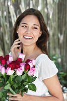 Happy young woman holding bunch of colorful roses