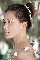 Side profile of a beautiful young woman wearing a shell necklace