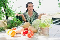Portrait of a mature woman sitting with vegetables on table