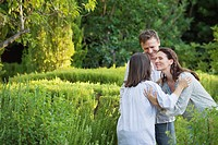 Mature couple hugging their mother in a garden