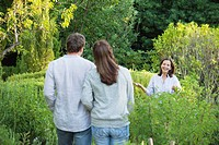 Mature couple walking towards their mother in a garden