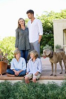 Family with their dog outside house
