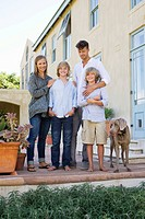 Portrait of a family standing together with their dog outside house