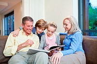 Grandparents and grandchildren on couch looking into book