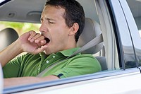 Mid adult man yawning while driving a car (thumbnail)
