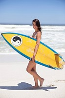 Woman walking on the beach with surfboard