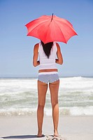 Woman standing on the beach with an umbrella and looking at sea view