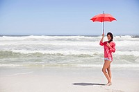 Woman standing on the beach with an umbrella
