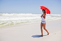 Woman walking on the beach with an umbrella