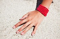 Close_up of a woman's hand on sand