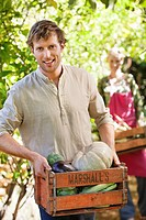Smiling man holding a crate of vegetables