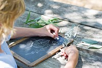 Side profile of a little boy making drawing of leaves on slate outdoors