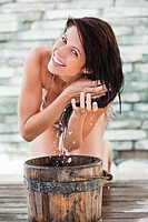 Portrait of a woman washing hair into a bucket (thumbnail)