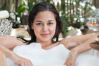 Portrait of a beautiful young woman taking bubble bath (thumbnail)