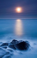 Night view of the moon rising over the sea