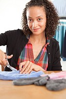 Attractive young woman cutting cloth