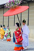 Costumed participants in the parade, some carrying red parasols for ladies walking beside them with the Imperial Palace in the background