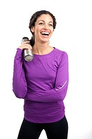 Attractive female runner holding metal bottle and laughing