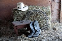 Some boots, a hat, a rope, and a bale of hay
