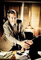 un uomo alla scrivania che stringe la mano ad una persona