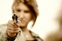 Young woman pointing gun