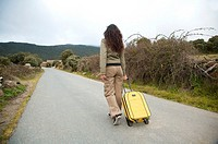 woman with suitcase on rural road at gredos mountains in avila spain