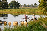 Boys with bicycles crossing a lake, Netherlands