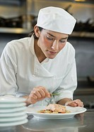 Female cook preparing food in commercial kitchen