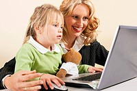 Businesswoman and mother showing kid the internet