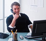 Man working on computer and talking on the phone at office