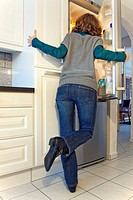 junge Frau schaut in den geöffneten Kühlschrank