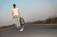 Young woman carrying suitcases on road, rear view