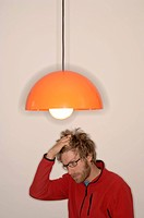 Young man with eyeglasses scratching his head in confusion under a lamp