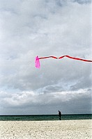 Person walking at Beach and pink Kite in the air _ Beach _ Warnemuende _ Mecklenburg_Western Pomerania _ Baltic Sea _ Germany