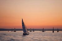 Germany, Lake Constance, Boat sailing on lake at dusk