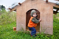 Little boy playing in dog house