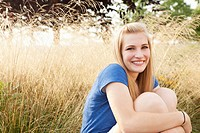 Caucasian teenager sitting in grass